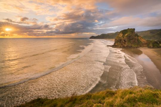 Catch the sunset at Piha Beach